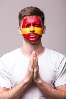 Junger spanischer mann-fußballfan mit gebetsgeste lokalisiert auf weißer wand