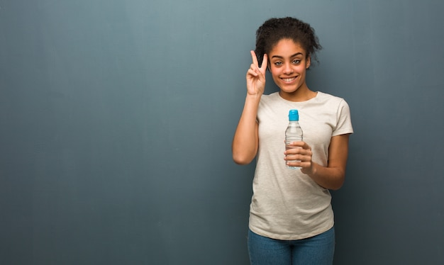 Junger spaß der schwarzen frau und glücklich, eine geste des sieges tuend. sie hält eine wasserflasche.