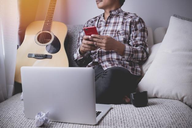 Junger spieler, der telefon auf weißer couch im wohnzimmer, konzept des komponierens von musik verwendet.