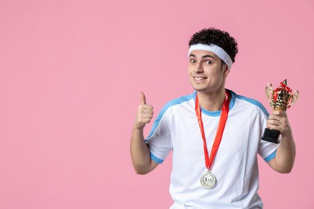 Junger spieler der vorderansicht in der sportkleidung mit goldener tasse auf rosa wand