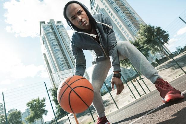 Junger spieler. ernsthafter afroamerikanischer mann, der sie beim basketballspielen ansieht