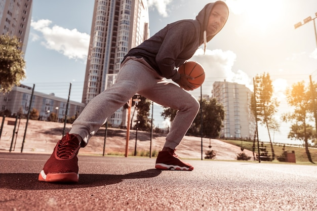 Junger spieler. niedriger winkel eines schönen jungen mannes, der einen ball hält, während er basketball spielt