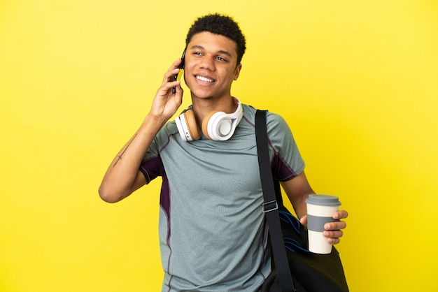 Junger sport-afroamerikaner mit sporttasche isoliert auf gelbem hintergrund, der kaffee zum mitnehmen und ein handy hält