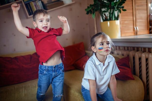 Junger sportfan schaut sich sportspiele an und jubelt ihrem team zu hause im fernsehen zu