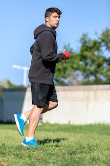 Junger sportfitnessmann draußen im park machen boxübungen.