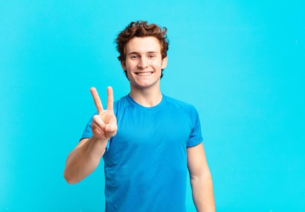 Junger sportjunge, der lächelt und freundlich aussieht, die nummer zwei oder die zweite mit der hand nach vorne zeigt, herunterzählt