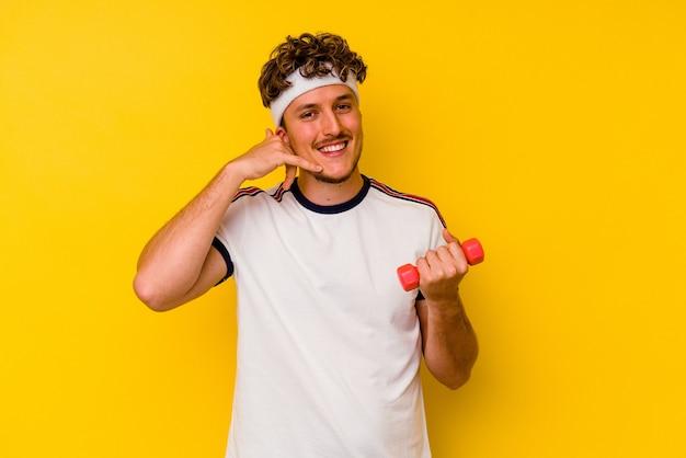 Junger sportkaukasiermann, der eine hantel lokalisiert auf einem gelben hintergrund hält, der eine handy-anrufgeste mit den fingern zeigt.