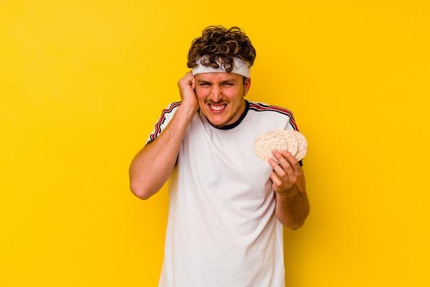 Junger sportkaukasiermann, der einen reiskuchen isst lokalisiert auf gelbem hintergrund, der ohren mit händen bedeckt.