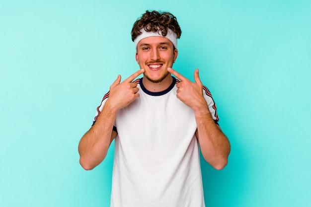 Junger sportkaukasiermann lokalisiert auf blauem hintergrund lächelt und zeigt finger auf mund.