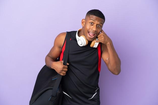Junger sportlateinmann mit sporttasche lokalisiert auf lila wand, die telefongeste macht. rufen sie mich zurück zeichen