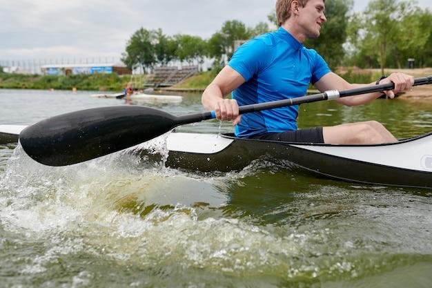 Junger sportler, der auf einem kanu paddelt