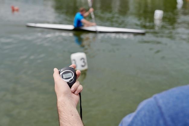 Junger sportler, der auf einem kanu und einer hand mit chronometer paddelt