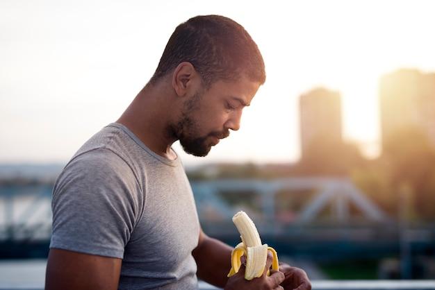 Junger sportler, der banane nach dem training isst