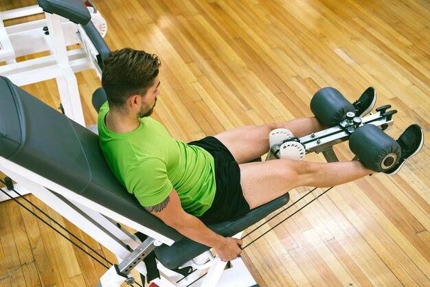 Junger sportler, der fast schreit, wenn er beinstreckung mit schwerem gewicht macht