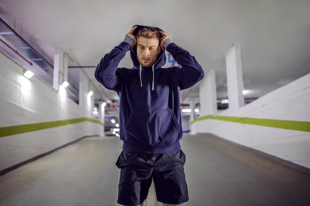 Junger sportler, der hoodie auf kopf setzt, während er in der tiefgarage steht.