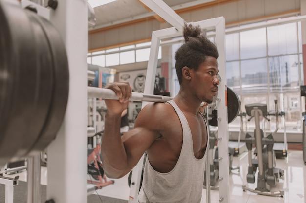 Junger sportler, der mit barbell ausarbeitet