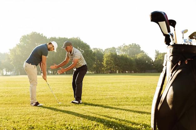 Junger sportler, der mit seinem lehrer golf übt
