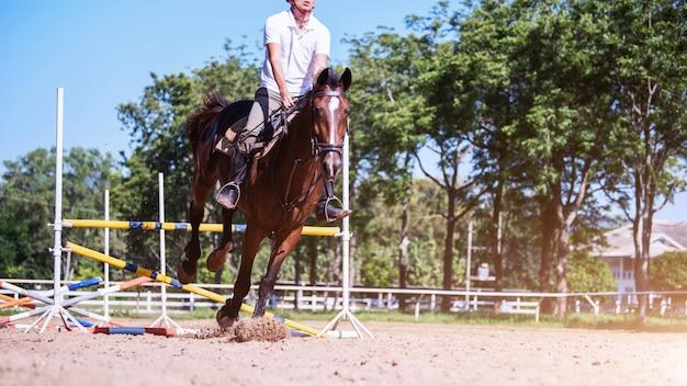 Junger sportler, der seinen kurs auf showpferdespringwettbewerb nimmt