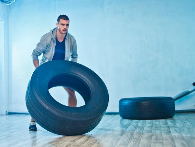 Junger sportler hebt ein großes gewichtsrad an. trainingsprozess. funktionstraining