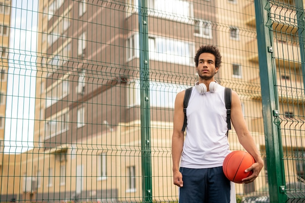 Junger sportler im weißen t-shirt mit ball für das spielen des basketballs, der durch den zaun um den hof steht