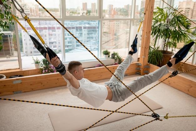 Junger sportler in aktivkleidung, der über der matte auf dem boden hängt, wobei seine arme und beine durch spezielle ausrüstung mit seilen befestigt werden