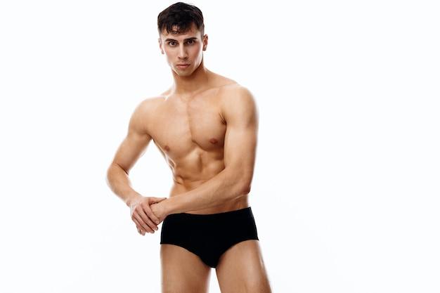 Junger sportler mit aufgepumptem oberkörper, der mit den händen auf hellem hintergrund gestikuliert