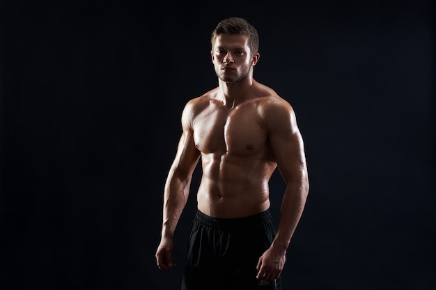 Junger sportler mit muskulöser passform, der ohne hemd auf schwarzem hintergrund posiert
