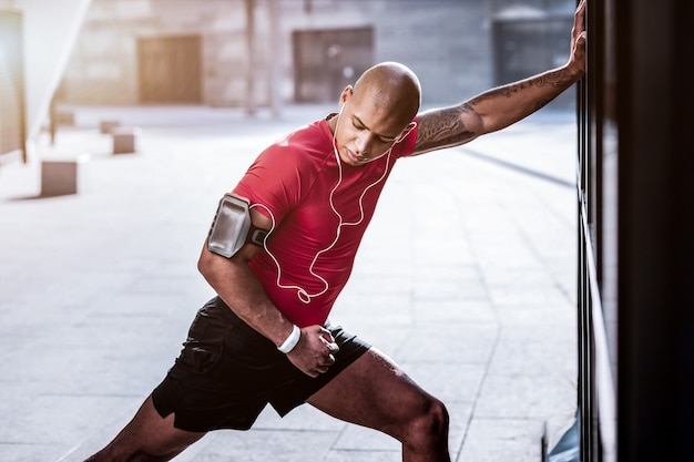 Junger sportler. netter afroamerikanischer mann, der seine hand streckt, während er sportliche aktivitäten ausführt