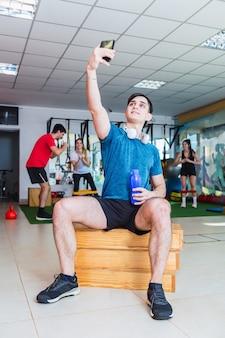 Junger sportler ruht im fitnessstudio. mann, der selfie an der turnhalle nimmt.
