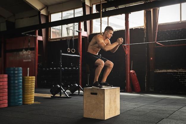 Junger sportler springt auf die box