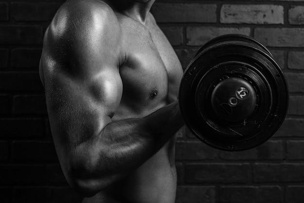 Junger sportler trainiert den bizeps im fitnessstudio vor einem dunklen hintergrund, nahaufnahme, schwarz und weiß