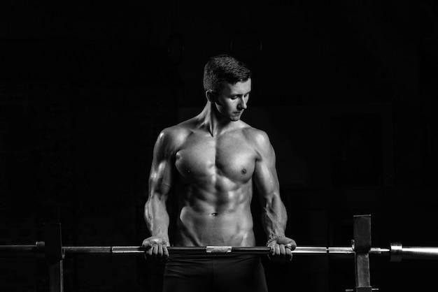 Junger sportler trainiert den bizeps im fitnessstudio vor einem dunklen hintergrund, schwarz und weiß