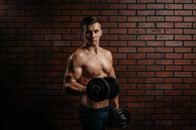 Junger sportler trainiert den bizeps im fitnessstudio vor einem dunklen hintergrund