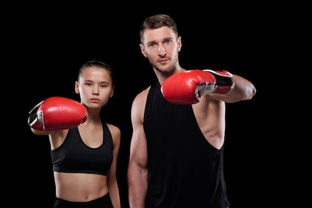 Junger sportler und sportlerin im training für aktivkleidung und boxhandschuhe