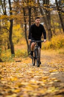 Junger sportlermann, der sportrad auf spur im herbstpark reitet
