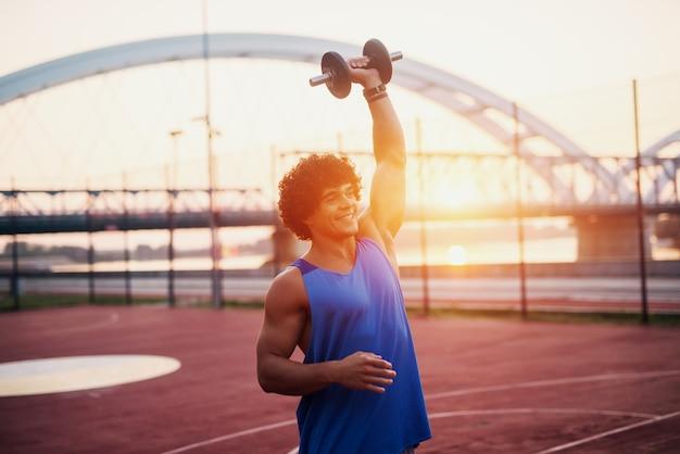 Junger sportlicher fit mann, der gewicht in seinem arm hält. außerhalb des trainings am frühen morgen.