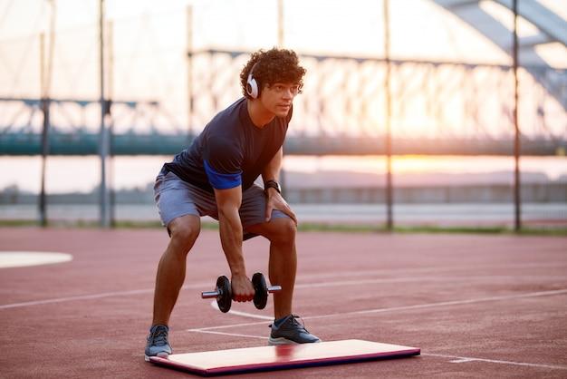 Junger sportlicher fit mann, der gewicht in seinem arm hält, während er die musik hört. außerhalb des trainings am frühen morgen.
