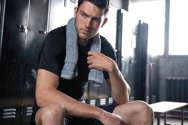 Junger sportlicher kaukasischer mann, der allein in der dunklen umkleidekabine des fitnessstudios sitzt und sich nach dem training ausruht.