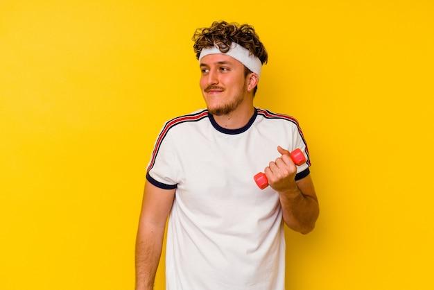 Junger sportlicher kaukasischer mann, der eine hantel einzeln auf gelbem hintergrund hält und davon träumt, ziele und zwecke zu erreichen