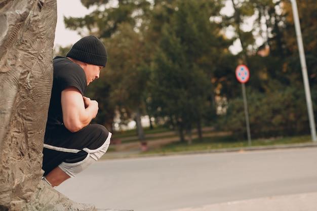 Junger sportlicher kerl, der parkour an der stadtstraße macht.