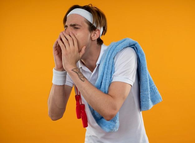 Junger sportlicher kerl mit geschlossenen augen, die stirnband mit armband mit springseil und handtuch auf schulter tragen, die jemanden lokalisiert auf gelber wand nennt