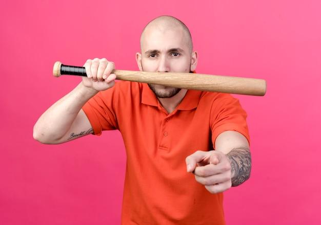 Junger sportlicher mann bedeckt mit baseballschlägermund und zeigt ihnen geste