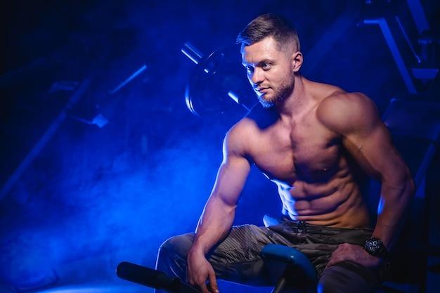 Junger sportlicher mann, der an der laufstrecke sitzt und sich nach hartem training auf einem stadion ausruht. blick auf die seite. nackter oberkörper muskulöser körper. nahaufnahme.
