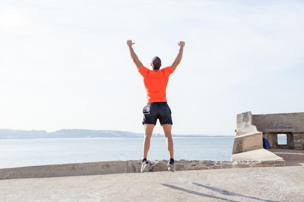 Junger sportlicher mann, der draußen im sommer springt