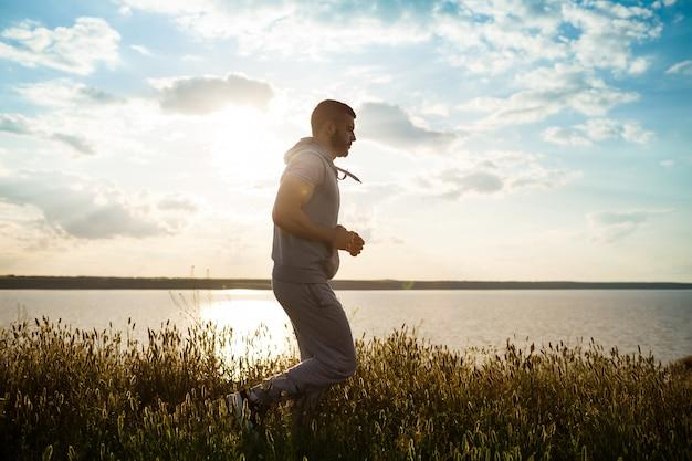 Junger sportlicher mann, der im feld bei sonnenaufgang joggt.