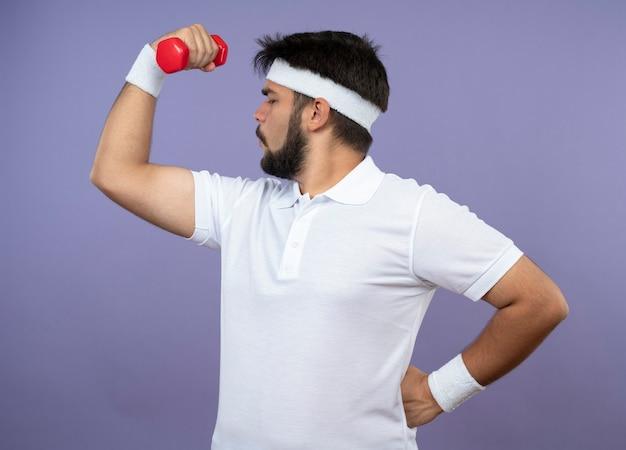 Junger sportlicher mann, der in der profilansicht das tragen des stirnbandes und des armbandes mit der hantel, die hand auf hüfte setzt, steht