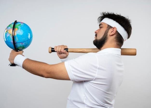Junger sportlicher mann, der in der profilansicht das tragen des stirnbandes und des armbandes steht, die baseballschläger auf schulter setzen und globus an der seite lokalisiert auf weißer wand halten
