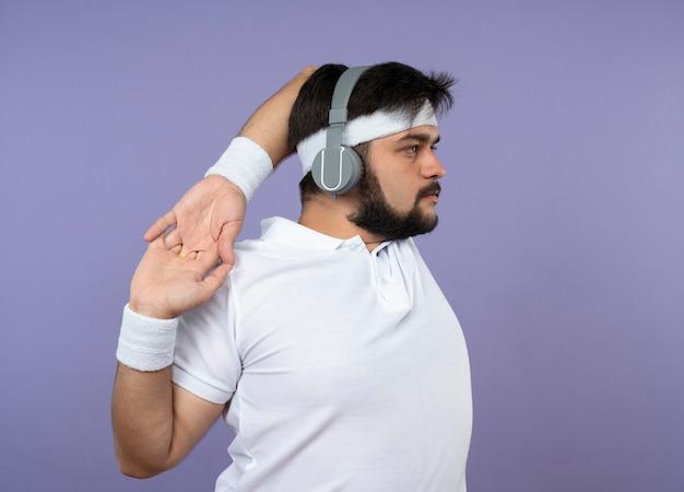 Junger sportlicher mann, der in der profilansicht steht und stirnband und armband mit kopfhörern trägt, die arm ausstrecken