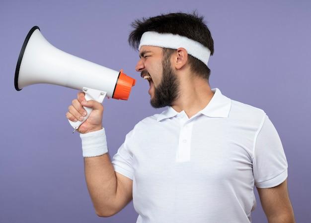 Junger sportlicher mann, der in der profilansicht steht und stirnband und armband trägt, spricht auf lautsprecher