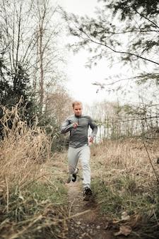Junger sportlicher mann, der in wald läuft